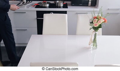 Man in the kitchen yourself serves white table for two persons.