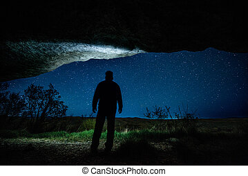 Man in the night grotto under a starry sky
