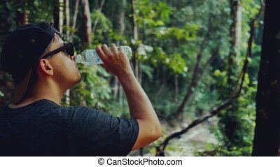 Man in the purchase of drinking water in a hot tropical forest