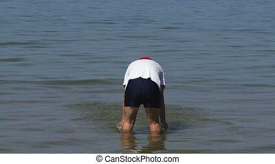 Man in the sea, splashing water up