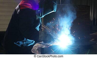 Man in the shop perform metal work - Medium tracking shot of...