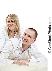 Man in the white shirt lies on the white shaggy carpet, woman sits near a little behind, their heads are turned a little aside.
