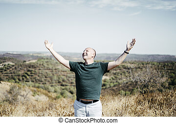 Man in the wilderness enjoying sun streching his arms up