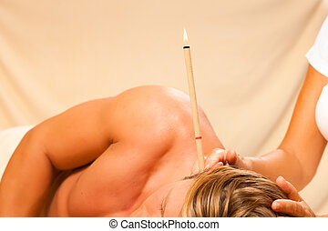Man in therapy with ear candles - Man in wellness and spa ...