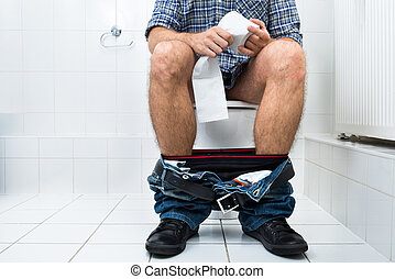 Close-up Of A Man Sitting On Commode Holding Tissue Paper Roll