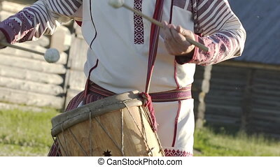 Man in traditional russian clothes dancing and playing on folklore drum outdoor on traditional antique wooden windmill background. Man wearing national Finno-Ugric clothes.