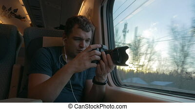 Man in train shooting footage and looking out the window -...