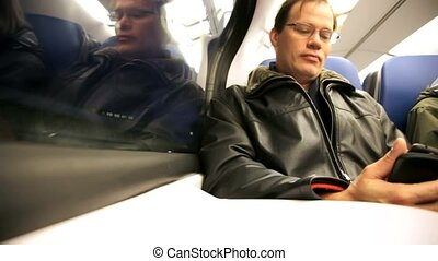 man in train with mobile by evening hour