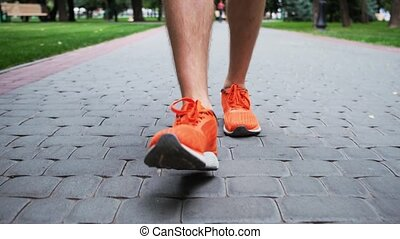 Man in orange trainers stepping along paved alley in city park