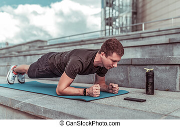 man in training summer city, stands emphasis lying down, plank, abs training, abdominal muscles, stretching flexibility, looks smartphone application phone timer, shaker with protein and water.