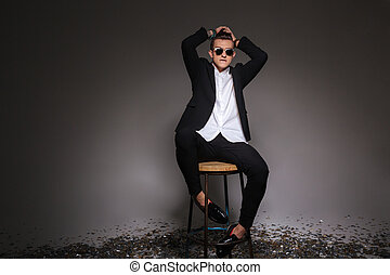 Man in trendy cloth sititng on the chair
