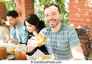 Man In Tshirt Having Cheeseburger At Restaurant