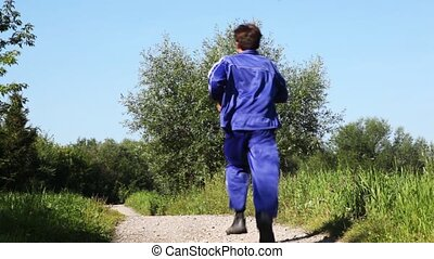 man in turn blue gym suits runs forward on lane in park in summer