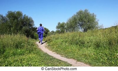 man in turn blue gym suits runs forward and back on lane in park