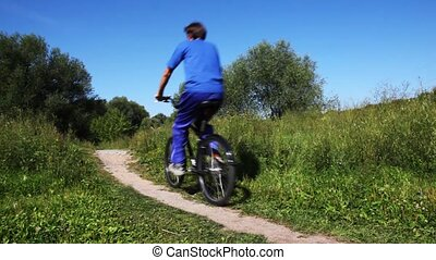 man in turn blue sports suit and boy in pink vest go forward one after another on bicycles on footpath in park