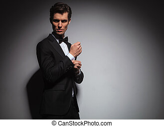 man in tuxedo arranging his sleeve looks back over shoulder