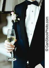 Man in tuxedo with boutonniere holds a champagne flute