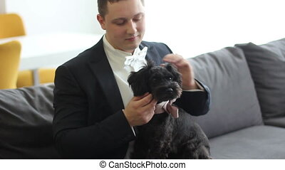 man in tuxedo with small dog.