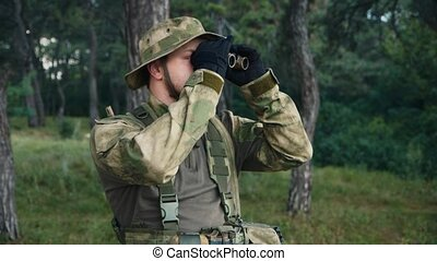 Man in uniform looking through binoculars. Airsoft game