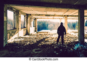 man in uniform with a gun in the ruins