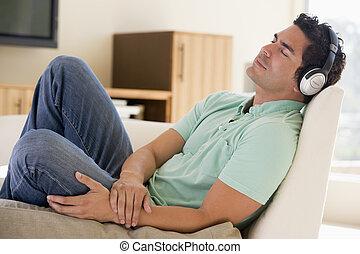 man, in, vardagsrum, lyssnande, till, hörlurar, sova