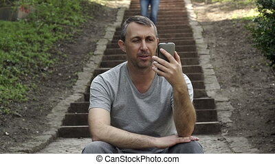 Man in Video Call on Outdoor Steps Woman Approaches - Man...
