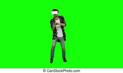 Man in virtual reality glasses and with joystick. Green...