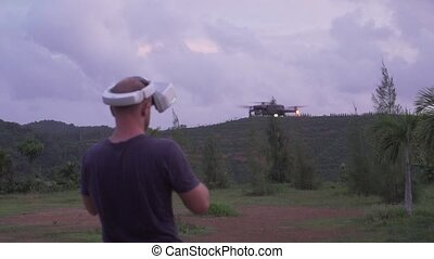 Man in virtual reality glasses controlling drone outdoors....