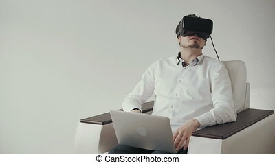 Man In Virtual Reality Glasses Using Laptop. Isolated on White Bckground