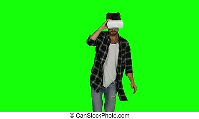 Man in VR a mask on his eyes. Green screen