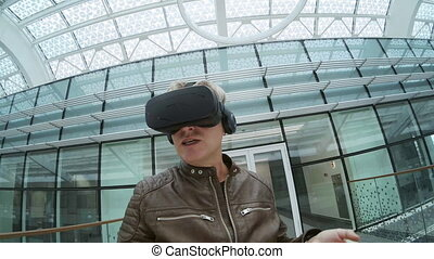 Modern male blogger wearing virtual reality headset taking selfie video and commenting opinion about gadget while walking in enclosed passage of contemporary building