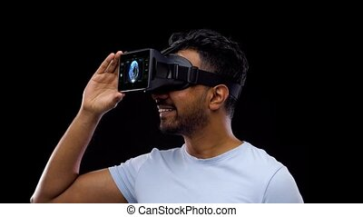 3d technology, future and people concept - young indian man in vr glasses or virtual reality headset with earth projection over black background