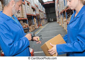 Man in warehouse wearing hand held scanner