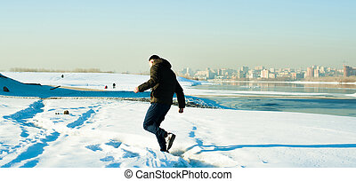 man in warm clothes with a beard is walking on the street in the winter in a warm sunny day at the river against the backdrop of the city