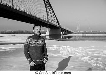 man in warm clothes with a beard is walking on the street in the winter in a warm sunny day at the river bridge in the background