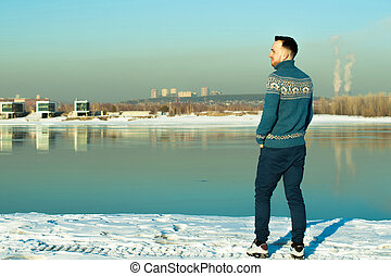 man in warm sweater with a beard is walking on the street in the winter in a warm sunny day at the river against the backdrop of the city