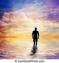 Man in water of calm ocean looking at the fairytale, fantastic sunset sky.