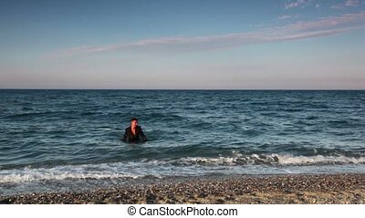 Man in wet suit going out from sea water - Man in brown wet...