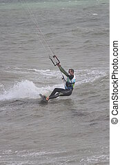 Man in wetsuit surfing with parachute, demonstrating daring, skill and talent.