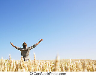 Man in Wheat Field With Arms Outstretched - Man standing in...