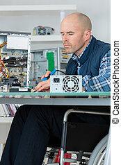 man in wheelchair fixing computer