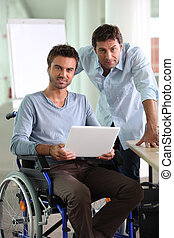 Man in wheelchair holding laptop