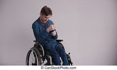 Man in wheelchair holding smartphone in his hands - Adult...