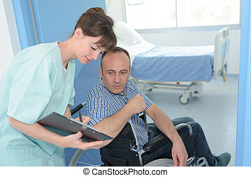 man in wheelchair in hospital with a nurse with clipboard