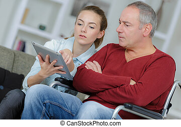 man in wheelchair learning to use a tablet