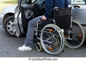 Man in wheelchair next to car - Man in a wheelchair next to...