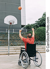 man in wheelchair playing basketball in the city