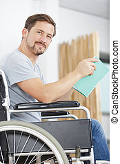 man in wheelchair reading book at home