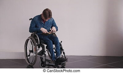 Man in wheelchair reading book at home - Young and disabled...