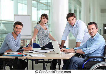 Man in wheelchair sat at desk with colleagues